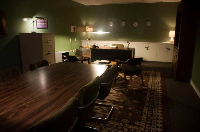 A 1960's themed room. It looks very spy craft. Timezone clocks hang on the walls, there is a large desk and conference room.
