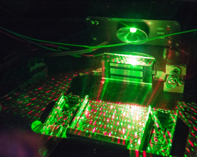 A projector shinging an array of green and red dots against a mirror. Wires, springs, magnets, and other mechanisms surround the projector.