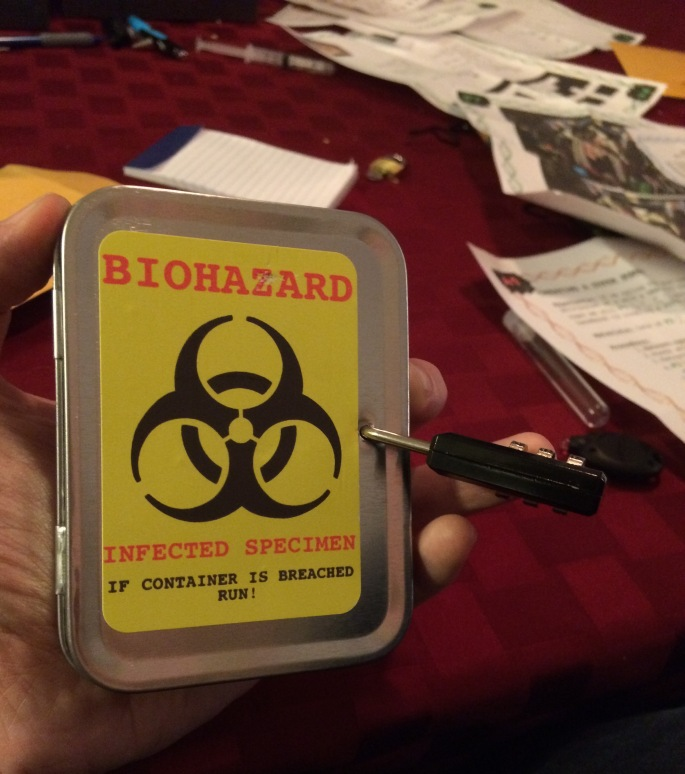 "A hand holding a locked tin labeld ""Biohazard. In the background is a table covered in paper and physical puzzles."