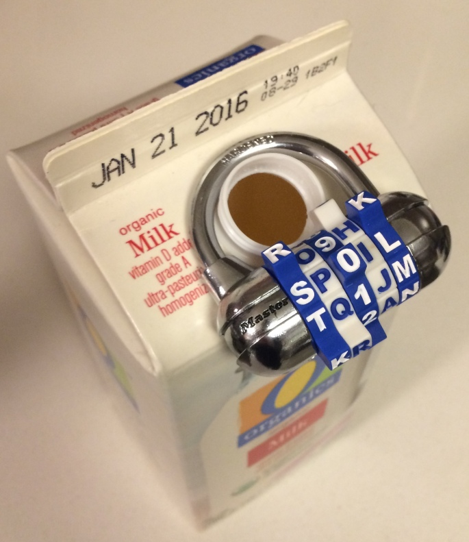 "An open quart of milk with a letter padloy hanging around the mouth of the bottle. The lock spells ""SPOIL."""
