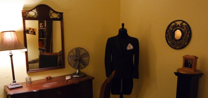 Interior of The Vanishing Act. Depicts a dressing room with a suit hanging elegantly.