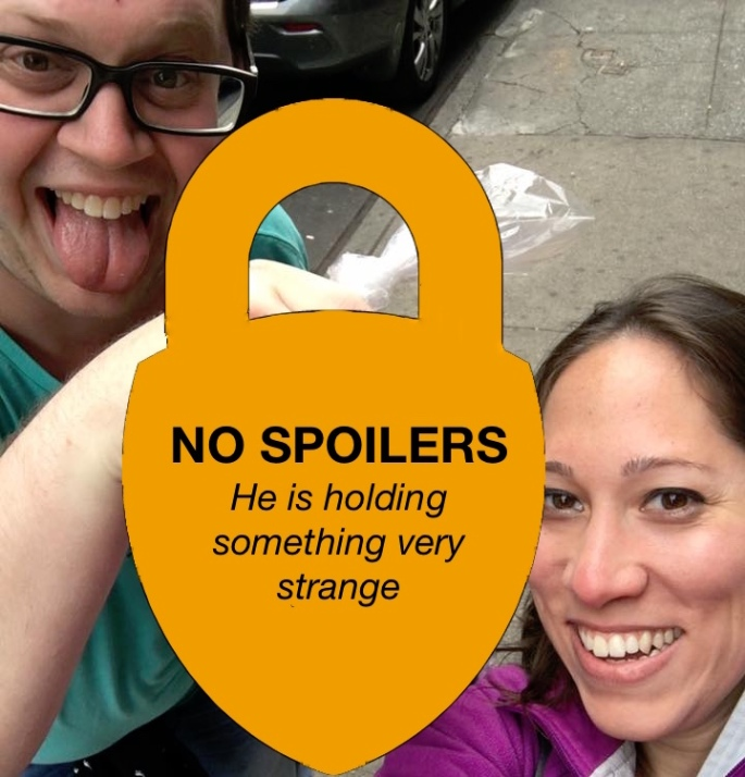 """A selfie of two people holding something. The object they are holding is obscured by a sign reading, """"No spoilers. He is holding something very strange."""""""