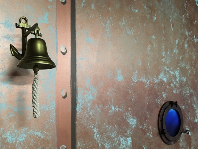 In-game: A wall painted to look like oxidized copper with a nautical bell hanging off of it, and a porthole embeded in it.