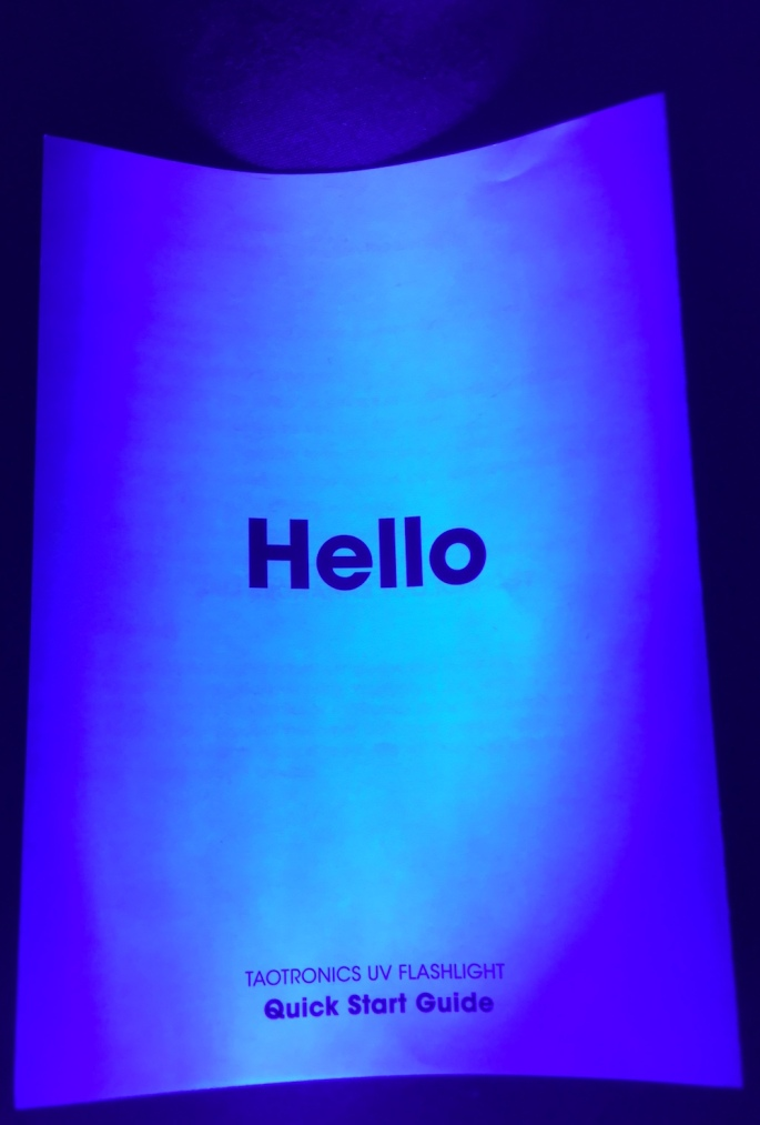 "The cover of the blacklight's instructions illuminated by the blacklight. It reads, ""Hello. Taotronics UV Flashlight. Quick Start Quide."""