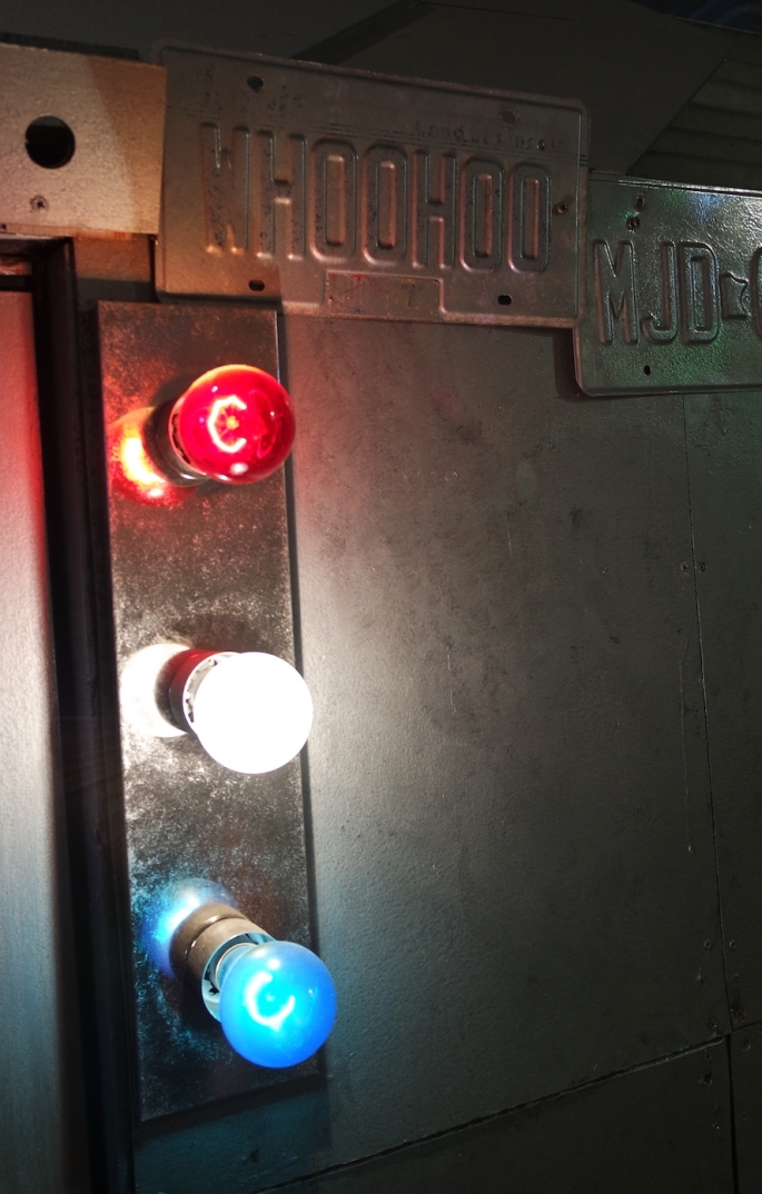 Close up shot of the outside of the railcar. Red, white, and blue lights illuminate a license plate that reads,