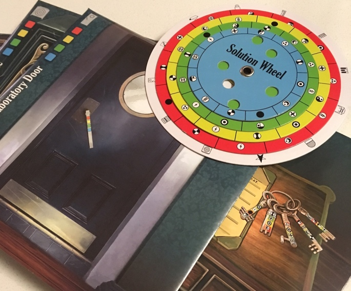 A pile of the puzzle envelopes from the game, along with the multi-color solution wheel. One envelope depices a heavy door, another shows a desk with an unusual and ornate set of keys resting atop it.