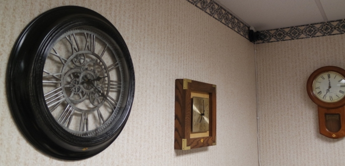 A bland wall with a number of differnt clocks hanging on it.
