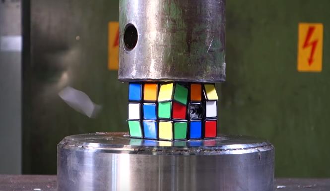 A hydraulic press starting to crush a Rubik's Cube.