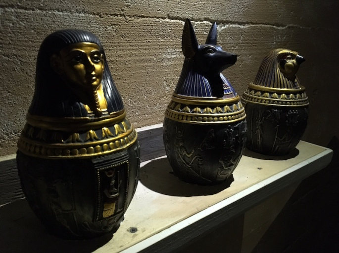A series of egyptian organ jars resting on a shelf.