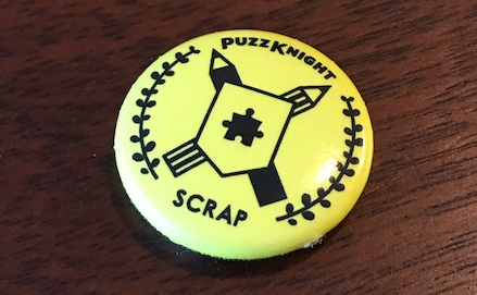 "A small yellow pin with a puzzle coat of arms. The pin reads, ""PuzzKnight SCRAP."""