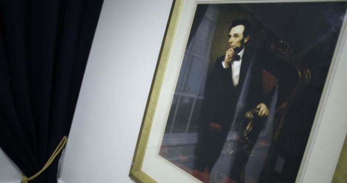 A white wall with a portrait of Lincoln mounted to it.