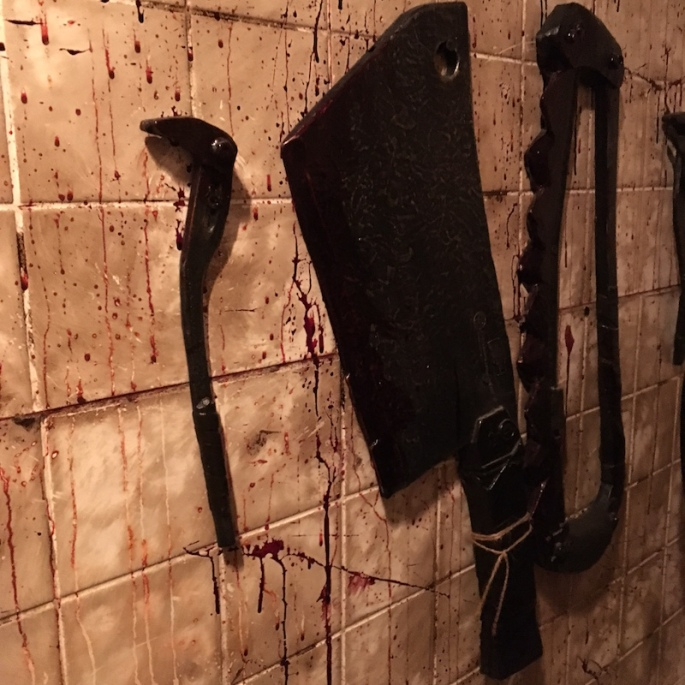 Bloodied cutting implements are mounted to a blood spattered tile wall.