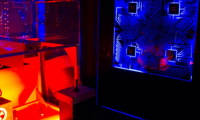 In-game, a non-repeating pattern appears illuminated in blue in the background, a cube with a joystick is illumminated in red in the foreground.