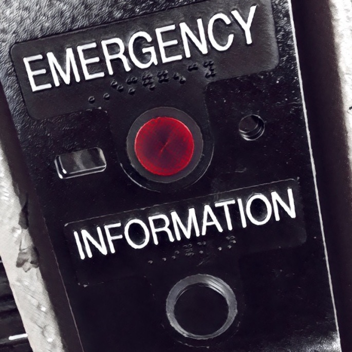 "Black and white image of an subway help panel. ""Emergency"" has a glowing red button. ""Information"" has a black button."