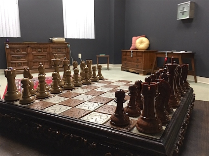 In-game: A pretty chess set sits in the foreground. A mundane room escape in the background.