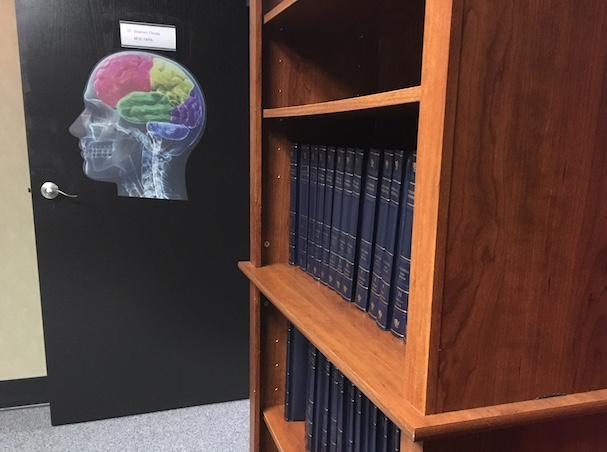 In-game: A bookcase with many volumes of an encyclopedia. A door in the background has a multi-color image of the human brain.