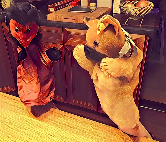 Stylized photo of a devil and dog puppets being held up from behind a table.