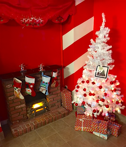 In-game - A fireplace with stockings hanging from it beside a white Christmas tree surrounded by presents.