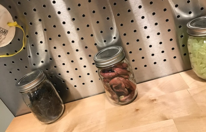 In-game: Closeup of a clean work bench with three jars on it. One with plastic spiders, a second with yellow stones, and a third with something that looks a little gross.