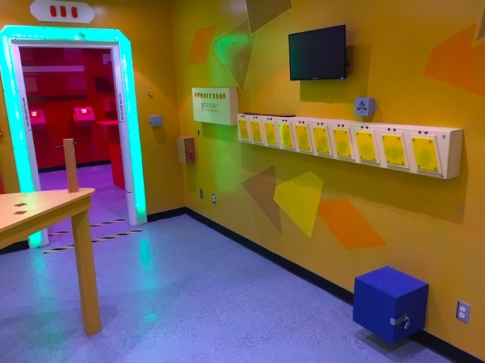 In-game: The Yellow Room features a variety of interactions colored yellow. A blue locked box is mounted to the wall in the foreground. The Red Room is through a glowing doorway in the background.