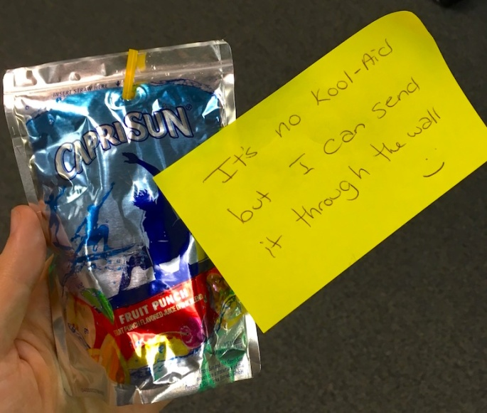"A CapriSun with a post it that reads, ""It's no Kool-Aid but I can send it through the wall :)"