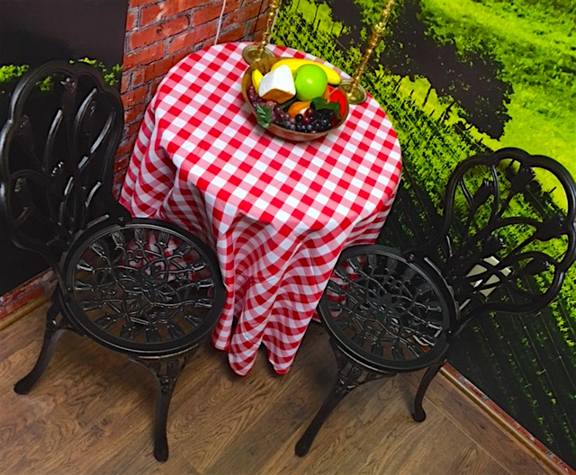 In-game: A table with a red & white checkered table cloth and two chairs. A bowl of fruit and cheese along with a pair of candle sticks rest atop the table.