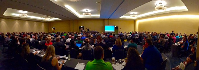 A panoramic photo of a room packed with 400 people listening to Lisa & David deliver their talk.