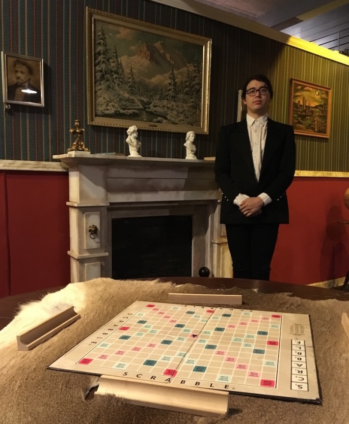 In-game: A scrabble board sitting on an animal pelt table cloth. A bellhop stands beside the mantle in the background, hands folded in front of him.