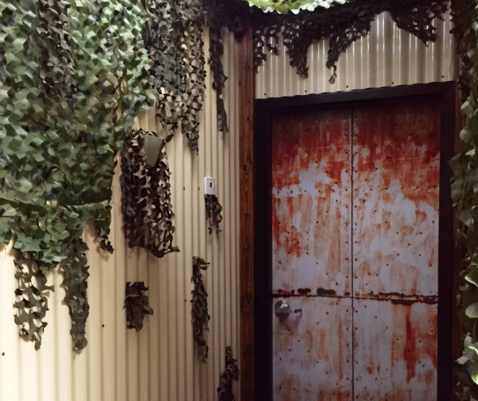 In game shot of a weathered metal door and corrugated aluminum walls.