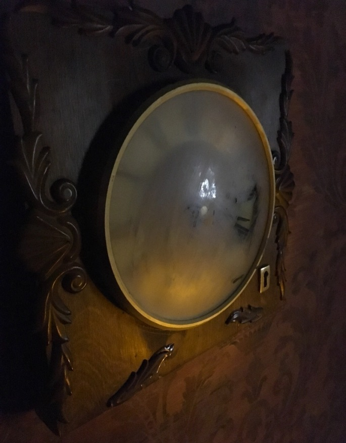 In-game closeup of an old clock with a lock built in. The clock face is is fogged over.
