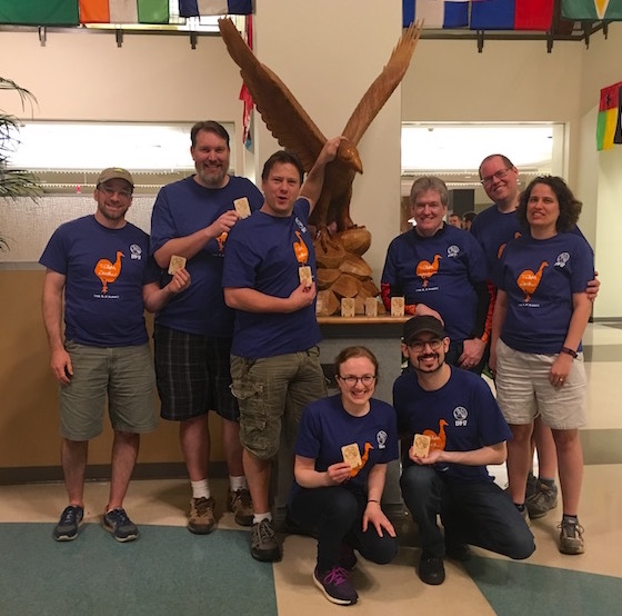 Team EMBU victory photo in the Auburn University Student Center. The team is gathered around the war eagle holding trophies.