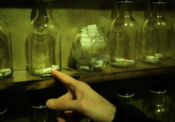 In-game: A hand interacting with glass bottles containing rolls of paper.