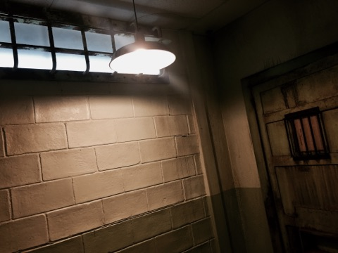 In game: A heavily weather concrete wall with a metal door. A light hangs about them.