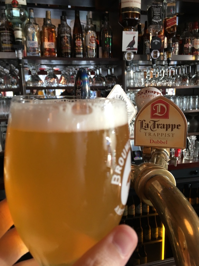 """A beer held up in front of a tap that reads, """"La Trappe: Trappist"""""""