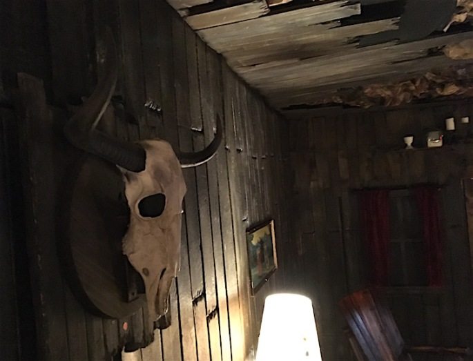 In game: A bull's skull hangs on a wood cabin wall, with a window and rocking chair in the background.