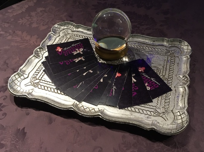 In-game: A metal platter with a crystal ball surrounded by Madame Neptune's Voodoo Curse cards.
