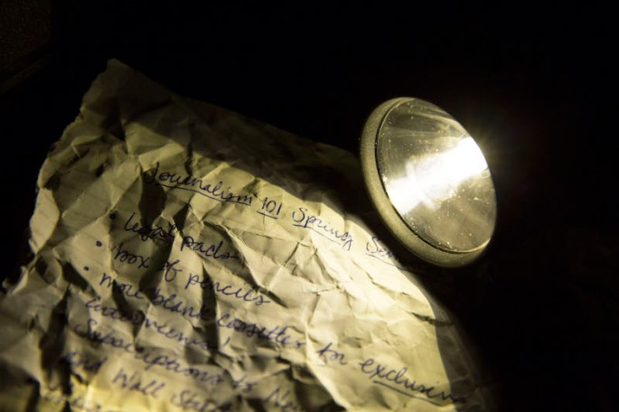 In-game: a closeup of a flashlight illuminating a crumpled piece of paper that appear to be notes from a journalism class.
